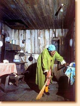 Old woman sweeping shack